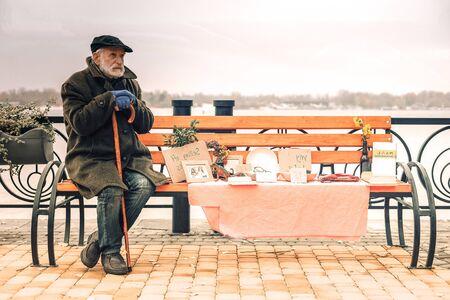 Pauvre froid misérable assis sur un banc dans un parc par beau temps