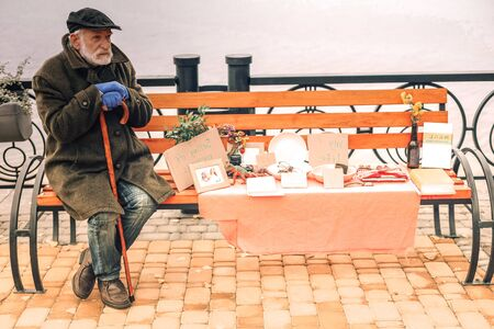 Lonely poor man with cane selling stuff in park on a fine day 写真素材