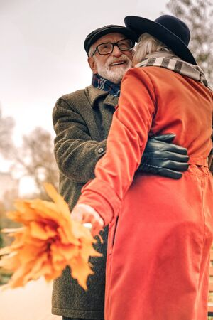 Low angle of a happy elderly couple hugging in park on a good day Stock Photo