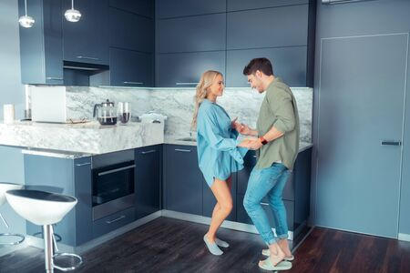 Dancing at home. Blonde-haired happy girlfriend dancing with her handsome man at home