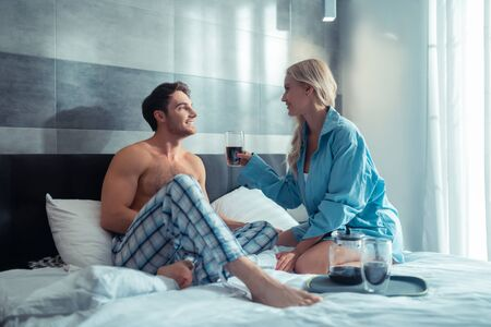 Cup of coffee. Blonde-haired appealing woman giving cup of coffee to her handsome man
