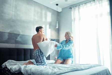 Couple having fun. Happy good-looking couple chilling and having fun while starting pillow fight Stock fotó
