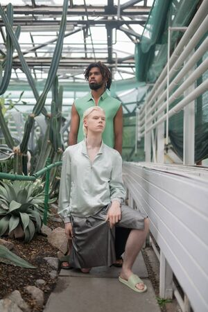 Extravagant clothing. Two male models wearing extravagant clothing posing in greenhouse 스톡 콘텐츠