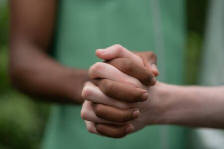 Holding hands together. Two young men with different skin color holding hands together