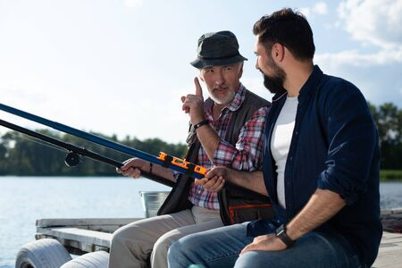 Teaching son. Bearded grey-haired man wearing checked shirt teaching son catching fish