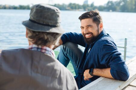 Businessman smiling. Handsome businessman smiling while talking to his dad sitting near lake Фото со стока