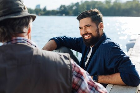 Morning with father. Beaming bearded man feeling happy spending morning with father near lake