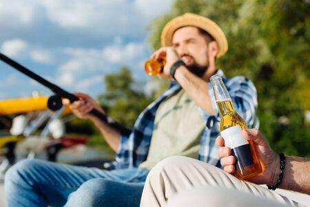Beber cerveza. Hijo guapo barbudo de pelo oscuro bebiendo una botella de cerveza mientras pesca con papá