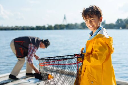 Nice fishing. Handsome boy smiling while fishing with grandfather in the morning
