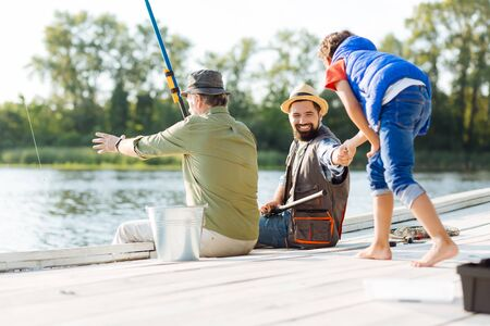 Family fishing. Men feeling happy while having family fishing on nice sunny day