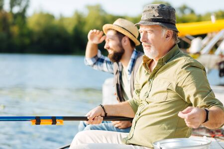 Sitting and fishing. Bearded retired man sitting near son and fishing in the morning