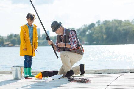 Preparing for fishing. Cute boy watching his grandfather preparing for fishing in the morning