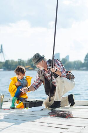 Fishing with grandson. Bearded grey-haired grandfather preparing for fishing with grandson