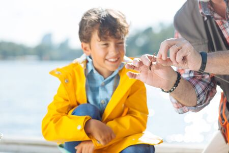 Worm on hook. Handsome dark-haired boy smiling while granddad putting worm on fishing hook