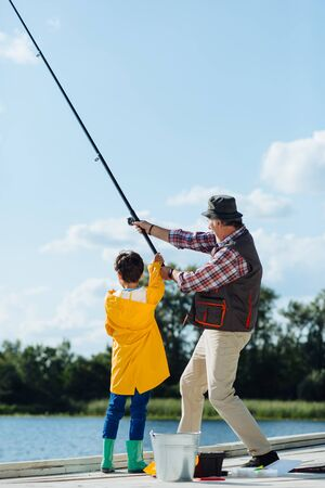 Pulling fishing tackle. Grandfather and boy pulling fishing tackle while fishing together in the morning