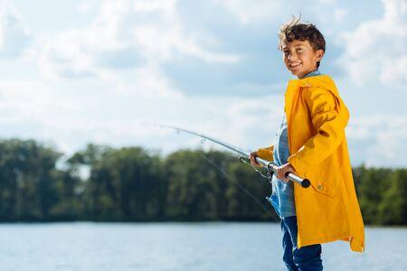 Fishing time. Handsome dark-haired boy wearing yellow rain coat smiling while fishing