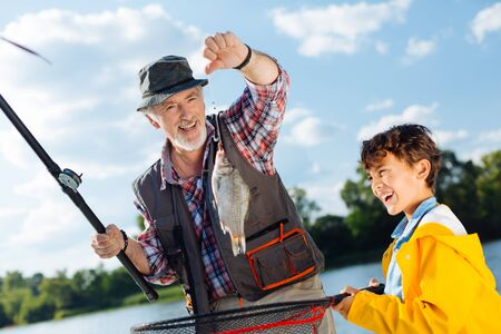 Grandson and grandfather feeling really happy after catching fish in the river