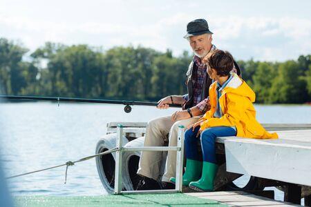 Escuchando al abuelo. Colegial de pelo oscuro escuchando a su abuelo barbudo mientras pesca