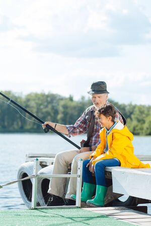 Grandfather fishing. Handsome boy wearing green rain boots smiling while watching grandfather fishing Stockfoto