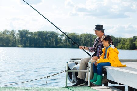 Dark-haired grandson wearing green rain boots learning how to fish with grandfather Banco de Imagens