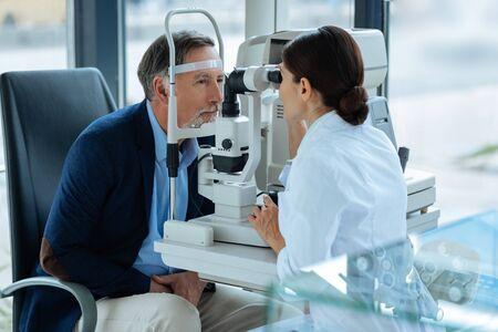 Für die Gesundheit sorgen. Netter alter Mann, der sein Sehvermögen überprüfen lässt, während er sich um seine Gesundheit kümmert Standard-Bild