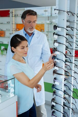 Helpful doctor. Professional male optician standing near his client while helping her to choose glasses Stockfoto