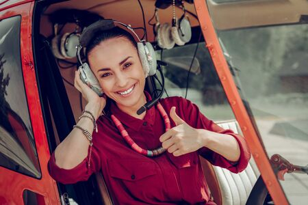 After successful flight. Dark-eyed prosperous young woman smiling broadly after successful flight in helicopter