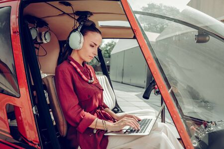 Laptop in helicopter. Busy successful woman finishing the report on laptop while sitting in helicopter Archivio Fotografico