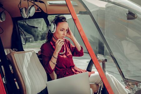 In the helicopter. Dark-haired stylish young businesswoman sitting in the private helicopter