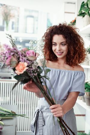 Light spring flowers. Cheerful short-haired curly girl correcting ikebana in her hands while having workday in flower shop