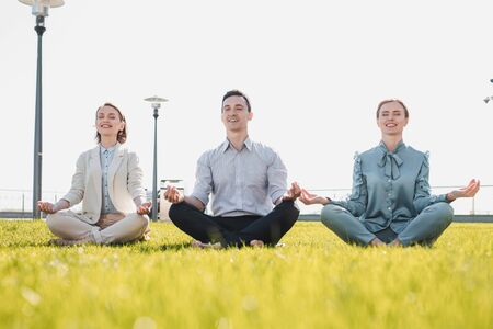 Reducing the stress. Office workers meditating together sitting on the grass Stockfoto