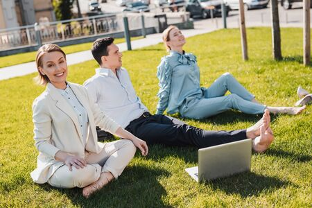 Spending time out of office. Colleagues sitting on the grass while working remotely Stockfoto - 129114500