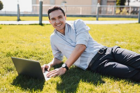 Working remotely. Man sitting on the grass with a notebook during the sunny weather Stockfoto - 129114505