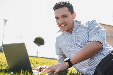 Doing business outdoor. A man is pleased with working on the grass Stockfoto - 129114508