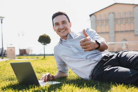 Unusual office. A man feeling good doing office tasks while laying on the grass Stockfoto - 129114504