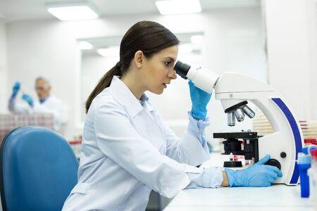 세심. 새로운 장비를 테스트하는 동안 반 위치에 앉아있는 매력적인 의료 종사자 스톡 콘텐츠