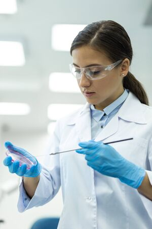 Reagent analysis. Pretty female person wearing protective glasses while working with chemical liquid 写真素材