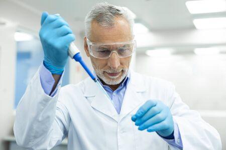 Muy contento. Persona del sexo masculino de pelo gris guapo manteniendo una sonrisa en su rostro mientras hace el experimento