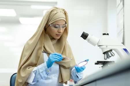 Indoors laboratory. Pleased Muslim researcher wearing protective glasses while doing experiment in lab
