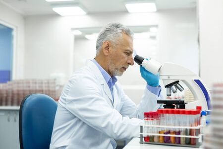 Be attentive. Cheerful mature medical worker looking at microscope while testing new equipment