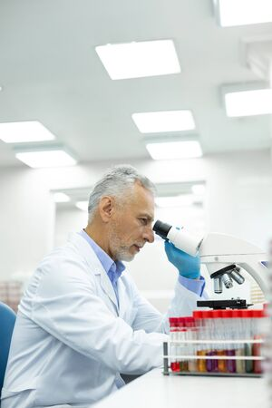 Protective gloves. Serious grey-haired man sitting in semi position and doing chemical experiment