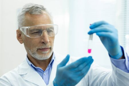 Precise glance. Serious researcher raising hands while checking reagent in test tube 写真素材 - 129801760