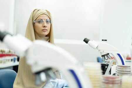 Have a look. Kind international researcher wearing protective glasses while working with reagents