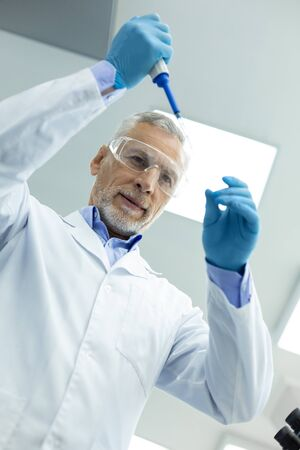 Biological experiment. Cheerful senior man wearing glasses while doing chemical research