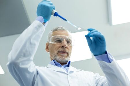 DNA analysis. Pleased bearded male person keeping smile on his face while checking DNA