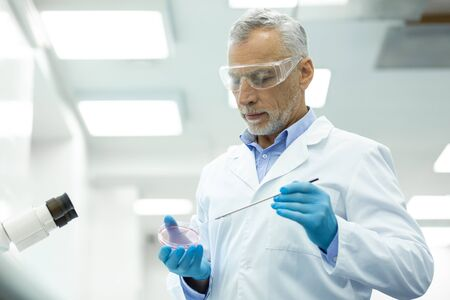 Thoughtful mood. Concentrated grey-haired man wearing uniform while controlling reaction on reagents