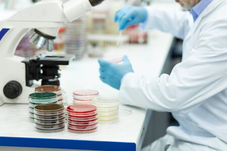 Need to think. Attentive man sitting in semi position while doing DNA analysis