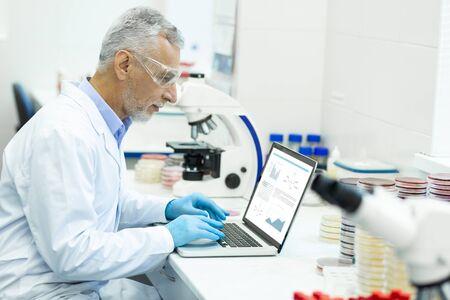 Proyecto científico. Grave hombre canoso sentado en posición semi y escribiendo artículo en su computadora portátil