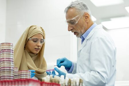 Being in al ears. Cheerful Muslim girl wearing hijab while working in laboratory 写真素材