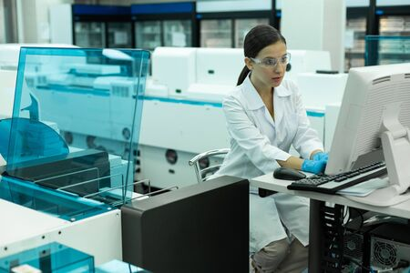 Modern investigation. Attractive young female wearing protective glasses while working in laboratory 写真素材